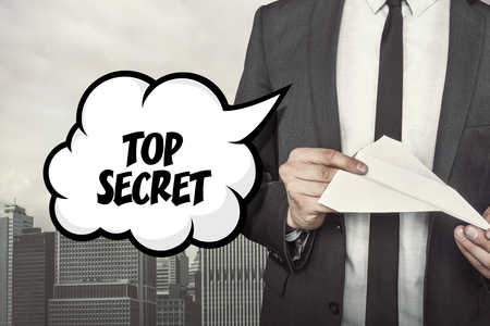 dependable: Top secret text on speech bubble with businessman holding paper plane in hand on city background