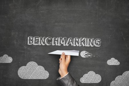 touchstone: Benchmarking concept on black blackboard with businessman hand holding paper plane