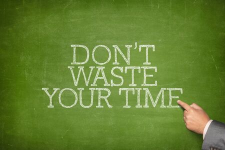 weaken: Dont waste your time text on blackboard with businessman hand pointing