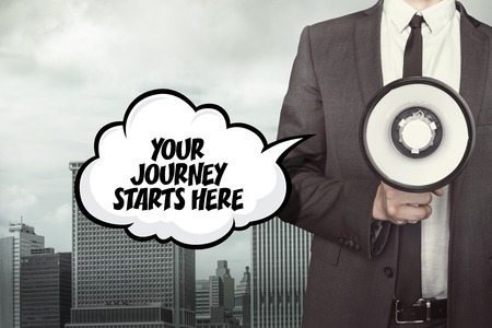 starts: Your journey starts here text on speech bubble with businessman and megaphone on city background Stock Photo