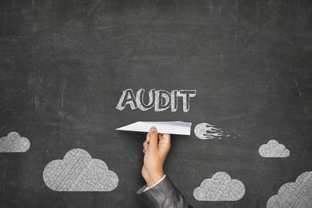audit: Audit concept on black blackboard with businessman hand holding paper plane