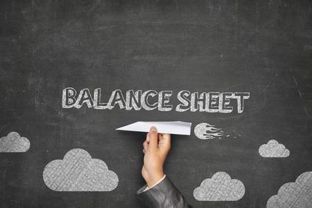stockholder: Balance sheet concept on black blackboard with businessman hand holding paper plane