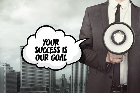 our: Your success is our goal text on speech bubble with businessman and megaphone on city background Stock Photo