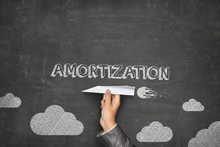 amortization: Amortization concept on black blackboard with businessman hand holding paper plane Stock Photo