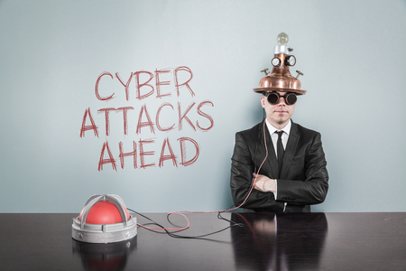 cyber attacks: Cyber attacks ahead concept with vintage businessman and calculator at office