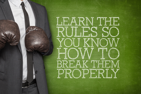 appropriately: Learn the rules so you know how to break them properly on blackboard with businessman wearing boxing gloves