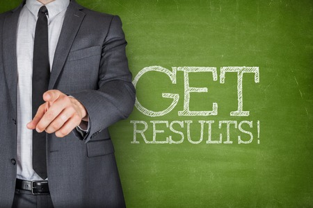 Get results on blackboard with businessman finger pointing Stock Photo