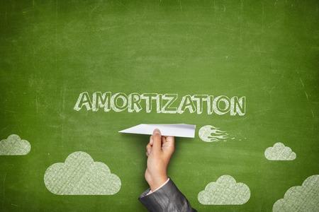 shrinkage: Amortization concept on black blackboard with businessman hand holding paper plane Stock Photo