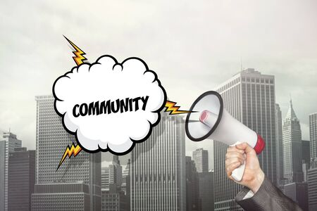 commune: Community text on speech bubble and businessman hand holding megaphone on cityscape background