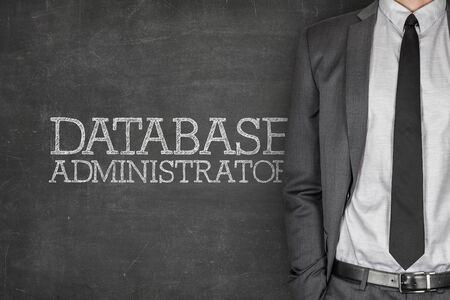 Database administrator on blackboard with businessman in a suit on side