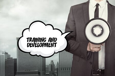 growth enhancement: Training and development text on speech bubble with businessman and megaphone on city background
