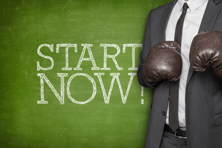 commencing: Start now on blackboard with businessman wearing boxing gloves Stock Photo
