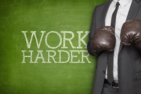 harder: Work harder on blackboard with businessman wearing boxing gloves