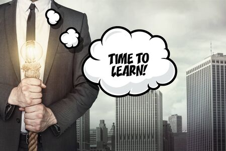 acquire: Time to learn text on speech bubble with businessman holding lamp on city background