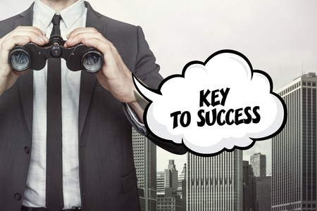 estimating: Key to success text on speech bubble with businessman holding binoculars on city background