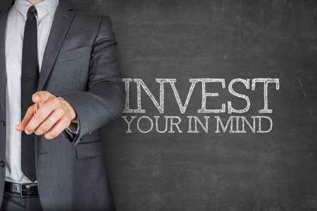 devote: Invest in your mind on blackboard with businessman finger pointing