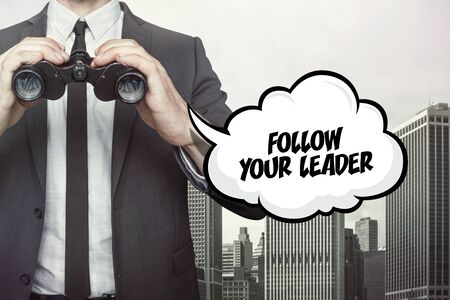 follow the leader: Follow your leader text on speech bubble with businessman holding binoculars on city background Stock Photo