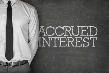 accrue: Accrued interest text on blackboard with businessman standing side Stock Photo