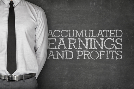 accrue: Accumulated earnings and profits text on blackboard with businessman standing side