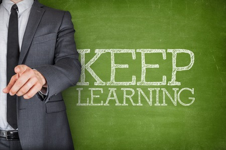 acquiring: Keep learning on blackboard with businessman finger pointing