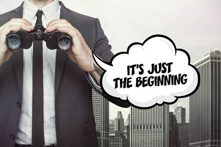 Its just the beginning text on speech bubble with businessman holding binoculars on city background