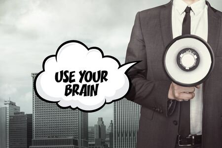 ability to speak: Use your brain text on speech bubble with businessman and megaphone on city background Stock Photo