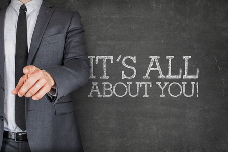 about you: Its all about you on blackboard with businessman finger pointing