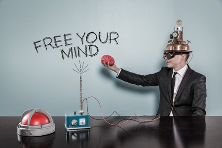 Mind power concept with businessman holding brain at hand in office