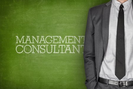 Management consultant on blackboard with businessman in a suit on side