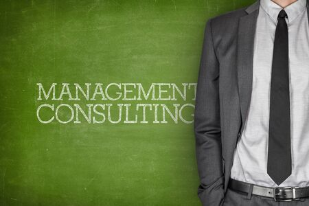 green board: Management consulting on blackboard with businessman in a suit on side