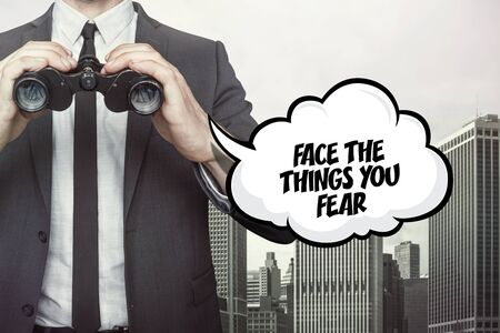 oppose: Face the things you fear text on speech bubble with businessman holding binoculars on city background
