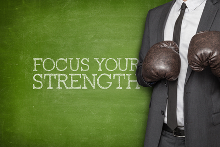 strenght: Focus your strenght on blackboard with businessman wearing boxing gloves