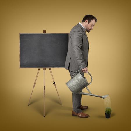 watering plant: Blank blackboard with businessman watering plant - studio shot