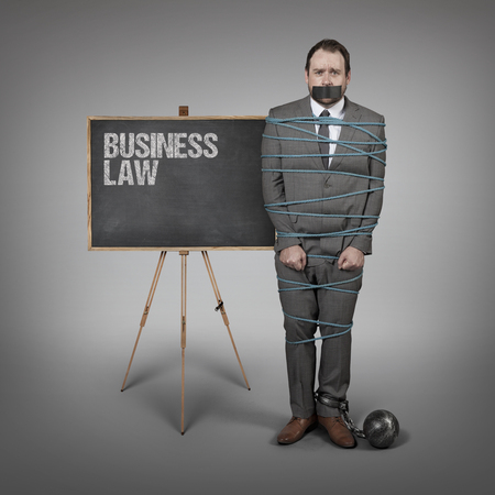 parameter: Businessman tied with rope - office setting with blackboard
