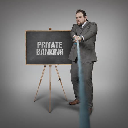 depositing: Businessman pulling rope with blackboard - studio shot