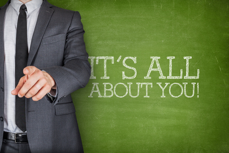 man business oriented: Its all about you on blackboard with businessman finger pointing