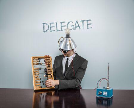 delegar: Delegar concepto de texto con el empresario y el �baco Foto de archivo