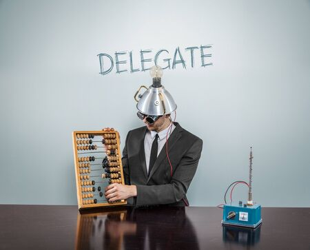 delegation: Delegate text concept with businessman and abacus