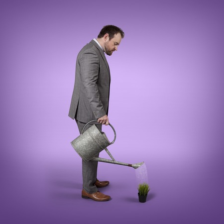 watering plant: Businessman watering plant with watering can indoor - studio shot