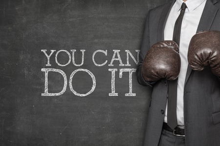 self assurance: You can do it on blackboard with businessman wearing boxing gloves Stock Photo