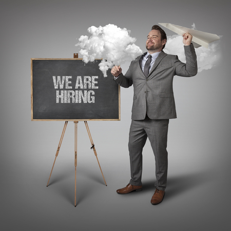 appointing: We are hiring text on blackboard with businessman and paper plane