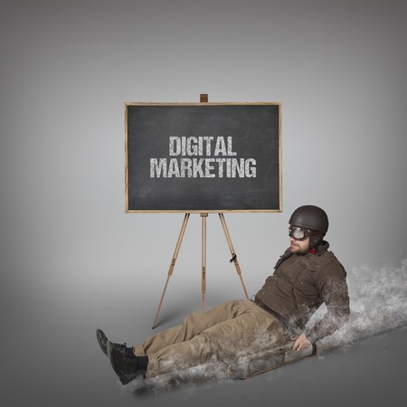 sledging people: Digital marketing text on blackboard with businessman sliding with a sledge