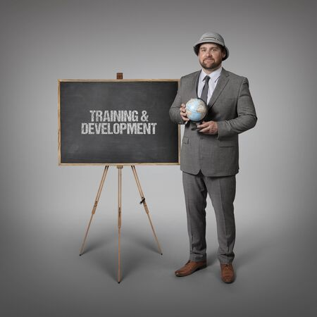 Training and development text on blackboard with businessman holding globe in hands