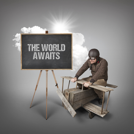 expects: The world awaits text on blackboard with businessman and wooden aeroplane Stock Photo