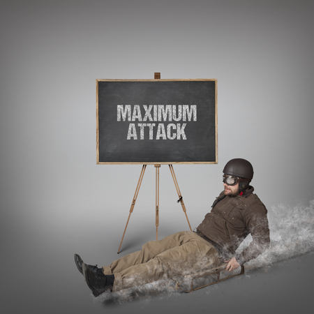 sledging people: Maximum attack text on blackboard with businessman sliding with a sledge Stock Photo
