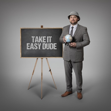 easygoing: Take it easy dude text on blackboard with businessman holding globe in hands