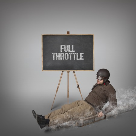 throttle: Full throttle text on blackboard with businessman sliding with a sledge