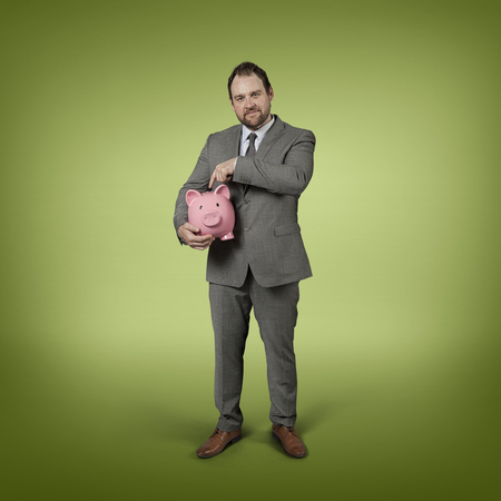 stylized banking: Businessman holding piggy bank with blank background