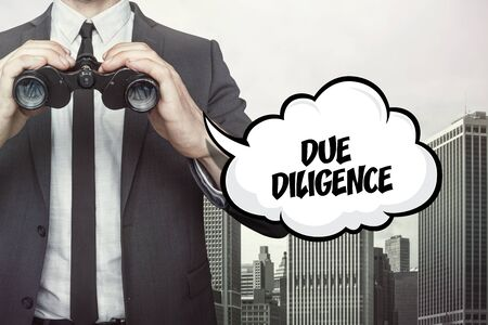 Due diligence text on speech bubble with businessman holding binoculars on city background Stock Photo
