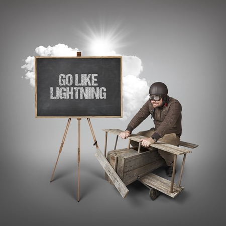 comparable: Go like lightning text on blackboard with businessman and wooden aeroplane